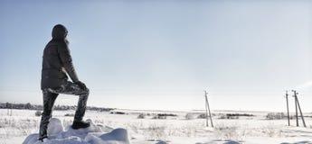 Οι άνθρωποι σκιαγραφιών στέκονται στο χειμερινό τομέα στην ηλιόλουστη ημέρα Στοκ Φωτογραφίες