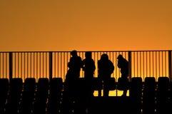 οι άνθρωποι σκιαγραφούν το ηλιοβασίλεμα σταδίων Στοκ Εικόνες
