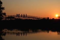 Οι άνθρωποι σκιών περπατούν πέρα από τη γέφυρα Στοκ Εικόνα