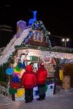 Οι άνθρωποι στέκονται κοντά στον αναμμένο στάβλο Χριστουγέννων στοκ εικόνα