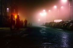 Οι άνθρωποι στέκονται τον περίπατο τη νύχτα μια ομιχλώδη ημέρα στην οδό στοκ εικόνες