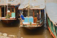 Οι άνθρωποι σταθμεύουν τις παραδοσιακές μακριές βάρκες στις όχθεις Mekong του ποταμού στη περίοδο ανομβρίας σε Luang Prabang, Λάο Στοκ εικόνα με δικαίωμα ελεύθερης χρήσης