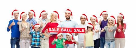 Οι άνθρωποι στα καπέλα santa με την πώληση υπογράφουν στα Χριστούγεννα στοκ φωτογραφία με δικαίωμα ελεύθερης χρήσης
