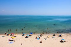 Οι άνθρωποι στηρίζονται στην παραλία στη θάλασσα στις διακοπές, κάνουν ηλιοθεραπεία, λούζουν Στοκ εικόνες με δικαίωμα ελεύθερης χρήσης
