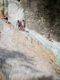 Οι άνθρωποι στηρίζονται στους θερμικούς αλατισμένους καταρράκτες των ορυκτών ελατηρίων Bagni SAN Filippo μια ηλιόλουστη ημέρα στοκ εικόνα με δικαίωμα ελεύθερης χρήσης