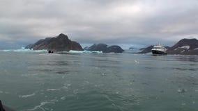 Οι άνθρωποι στη βάρκα πλέουν και μεγάλο γιοτ στο υπόβαθρο των χιονωδών βουνών στην Αρκτική απόθεμα βίντεο