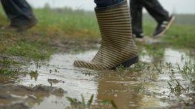 Οι άνθρωποι στις λαστιχένιες μπότες είναι στο έδαφος Πόδια στη λαστιχένια λακκούβα βροχής μποτών Οι άνθρωποι στις λαστιχένιες μπό Στοκ φωτογραφία με δικαίωμα ελεύθερης χρήσης