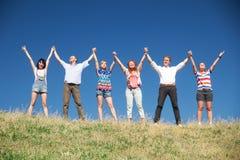 Οι άνθρωποι στο λόφο αυξάνουν τα χέρια από κοινού Στοκ εικόνες με δικαίωμα ελεύθερης χρήσης