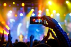 Οι άνθρωποι στο πλήθος σε μια συναυλία κάνουν τις τηλεοπτικές καταγραφές και pics σε ένα smartphone στοκ εικόνα