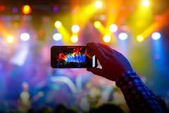 Οι άνθρωποι στο πλήθος σε μια συναυλία κάνουν τις τηλεοπτικές καταγραφές και pics σε ένα smartphone στοκ εικόνες