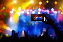 Οι άνθρωποι στο πλήθος σε μια συναυλία κάνουν τις τηλεοπτικές καταγραφές και pics σε ένα smartphone στοκ φωτογραφία με δικαίωμα ελεύθερης χρήσης