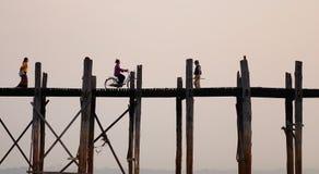 Οι άνθρωποι στο Ubein γεφυρώνουν στο ηλιοβασίλεμα στο Μιανμάρ Στοκ Φωτογραφία