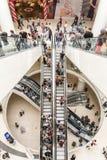 Οι άνθρωποι συσσωρεύουν στις κυλιόμενες σκάλες στη λεωφόρο αγορών πολυτέλειας Στοκ Φωτογραφία