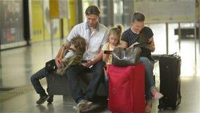 Οι άνθρωποι τετραμελών οικογενειών περιμένουν στο σιδηροδρομικό σταθμό ή έναν αερολιμένα με τις μεγάλες τσάντες Οι γονείς και τα  απόθεμα βίντεο