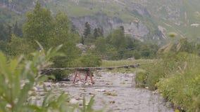 Οι άνθρωποι τουριστών με τα backpaks που περπατούν στην αναστολή γεφυρώνουν πέρα από τον ποταμό βουνών απόθεμα βίντεο