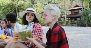 Οι άνθρωποι τρώνε τα τροπικά φρούτα και πίνουν τα κοκτέιλ καρύδων που μιλούν κάθονται πέρα από τους φοίνικες, τους ευτυχείς άνδρε απόθεμα βίντεο