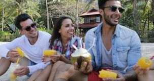 Οι άνθρωποι τρώνε τα τροπικά φρούτα και πίνουν τα κοκτέιλ καρύδων που μιλούν κάθονται πέρα από τους φοίνικες, τους ευτυχείς άνδρε φιλμ μικρού μήκους