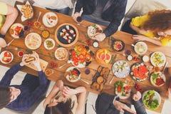 Οι άνθρωποι τρώνε τα υγιή γεύματα και τη συζήτηση στο εξυπηρετούμενο κόμμα επιτραπέζιων γευμάτων στοκ εικόνες