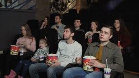 Οι άνθρωποι τρώνε popcorn και προσέχουν έναν κινηματογράφο στον κινηματογράφο απόθεμα βίντεο