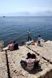 Οι άνθρωποι χαλαρώνουν σε ένα τμήμα του seawall σε Kaleici σε Antalya στην Τουρκία Στοκ Εικόνες