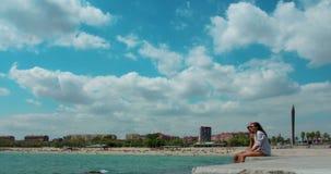 Οι άνθρωποι χαλαρώνουν στην παραλία της Βαρκελώνης Χρονικό σφάλμα των άσπρων σύννεφων στον ουρανό πέρα από την μπλε θάλασσα απόθεμα βίντεο