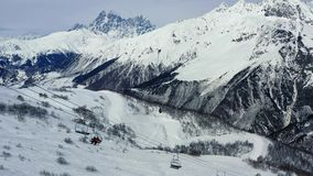 Οι άνθρωποι χρησιμοποιούν έναν ανελκυστήρα σκι για να φτάσουν στην κορυφή ενός βουνού, που ζαλίζει το βουνό στο υπόβαθρο, 4k απόθεμα βίντεο