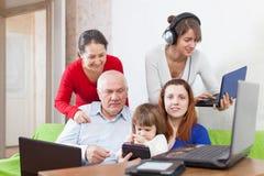 Οι άνθρωποι χρησιμοποιούν λίγες ηλεκτρονικές συσκευές στο σπίτι Στοκ Εικόνα