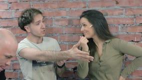 Οι άνδρες και η ενήλικη γυναίκα πυροβολούν κάποιο στη κάμερα διαδικασία διαμάχη κόκκινο με την άσπρη ένωση φιλμ μικρού μήκους