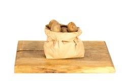 Οι άπλυτες πατάτες σε μια τσάντα εγγράφου στο λευκό Στοκ Φωτογραφίες