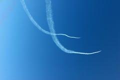 Οι άσπρες γραμμές καμπυλών πνίγουν με το αεροπλάνο στην οριζόντια άποψη υποβάθρου μπλε ουρανού Στοκ εικόνα με δικαίωμα ελεύθερης χρήσης