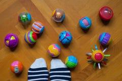 Οι άσπρες μπλε κίτρινες κόκκινες κατασκευές κύβων λωρίδων καλτσών ποδιών μπερδεύουν το πάτωμα παιχνιδιών παιχνιδιών ξύλινο στοκ φωτογραφία με δικαίωμα ελεύθερης χρήσης