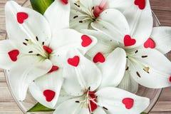 Οι άσπροι κρίνοι με τις μικρότερες κόκκινες καρδιές στο γυαλί κυλούν, κοιλάδα Στοκ Φωτογραφίες