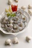 Οι άψητες ακατέργαστες headless γαρίδες με το λεμόνι τεμαχίζουν και ντομάτα στο άσπρο πιάτο με το άσπρο υπόβαθρο Στοκ Φωτογραφίες