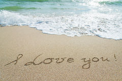 Οι λέξεις περιγράφουν σ' αγαπώ στην υγρή άμμο με το κύμα Στοκ φωτογραφίες με δικαίωμα ελεύθερης χρήσης