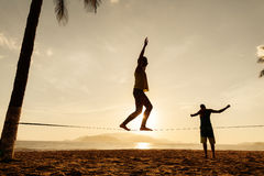 Οι έφηβοι ισορροπούν στη σκιαγραφία slackline Στοκ εικόνα με δικαίωμα ελεύθερης χρήσης