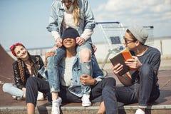 Οι έφηβοι ομαδοποιούν να καθίσουν μαζί στην κεκλιμένη ράμπα και την κατοχή της διασκέδασης στοκ εικόνες