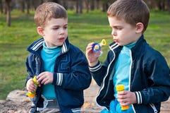 Οι ίδιοι δίδυμοι αδερφοί φυσούν τις φυσαλίδες σαπουνιών Στοκ Εικόνες