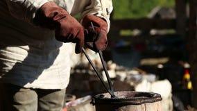 Οι λαβίδες σφυρηλατημένων κομματιών σιδηρουργών διορθώνουν τη χοάνη στο φούρνο απόθεμα βίντεο