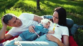 Οι αγαπώντας γονείς με λίγη κόρη στηρίζονται στο κάλυμμα στην πράσινη χλόη στο ηλιόλουστο πάρκο απόθεμα βίντεο