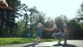 Οι αγαπώντας γονείς με την κόρη μικρών παιδιών ξοδεύουν τον ελεύθερο χρόνο στο θερινό κήπο απόθεμα βίντεο