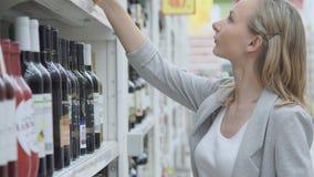 Οι αγορές γυναικών για το κρασί ή άλλο οινόπνευμα σε ένα μπουκάλι αποθηκεύουν τη στάση μπροστά από το σύνολο ραφιών των μπουκαλιώ φιλμ μικρού μήκους