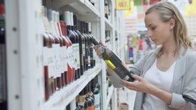 Οι αγορές γυναικών για το κρασί ή άλλο οινόπνευμα σε ένα μπουκάλι αποθηκεύουν τη στάση μπροστά από το σύνολο ραφιών των μπουκαλιώ απόθεμα βίντεο