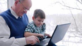 Οι αγορές Διαδικτύου, ο ηληκιωμένος με την πλαστική κάρτα και το παιδί κάνουν τις σε απευθείας σύνδεση αγορές μέσω του lap-top στ απόθεμα βίντεο