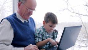Οι αγορές Διαδικτύου, granddad με το παιδί υπολογίζονται από τα ηλεκτρονικά χρήματα μέσω του lap-top στο εσωτερικό απόθεμα βίντεο