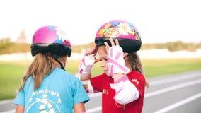 Οι αδελφές βοηθούν η μια την άλλη για να φορέσουν ένα προστατευτικό κράνος απόθεμα βίντεο