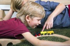 Οι αδελφοί παίζουν με το ξύλινο τραίνο, χτίζουν το σιδηρόδρομο παιχνιδιών στο σπίτι ή το δ στοκ εικόνα με δικαίωμα ελεύθερης χρήσης