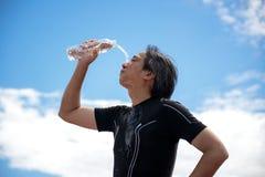 Οι αθλητές αθλητών χύνουν στο νερό στα πρόσωπα και την εκμετάλλευσή τους ένα πόσιμο νερό μπουκαλιών νερό μετά από την άσκηση, πίσ Στοκ Εικόνα