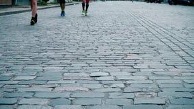Οι αθλητές τρέχουν κατά μήκος του στρωμένου δρόμου πετρών, μαραθώνιος πόλεων, κινηματογράφηση σε πρώτο πλάνο ποδιών δρομέων `, αθ φιλμ μικρού μήκους