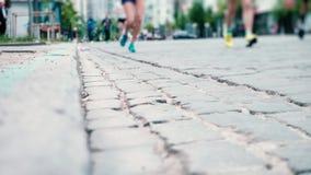 Οι αθλητές τρέχουν κατά μήκος του στρωμένου δρόμου πετρών, μαραθώνιος πόλεων, κινηματογράφηση σε πρώτο πλάνο ποδιών δρομέων `, αθ απόθεμα βίντεο