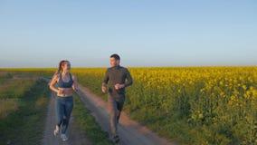 Οι αθλητικές δραστηριότητες, το εύθυμα άτομο αθλητών και το θηλυκό με τις πλεξούδες kanekalon τρέχουν γύρω στη φύση στο λιβάδι βι απόθεμα βίντεο
